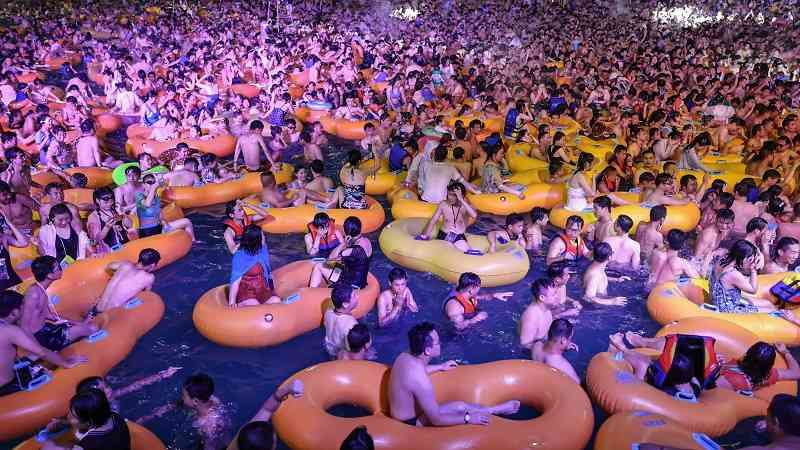 large number of people in a pool at a water park