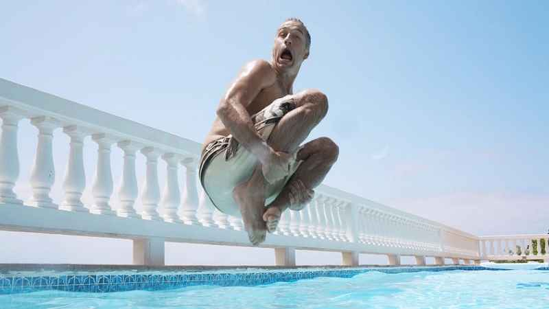 man doing a cannonball jump into a swimming pool